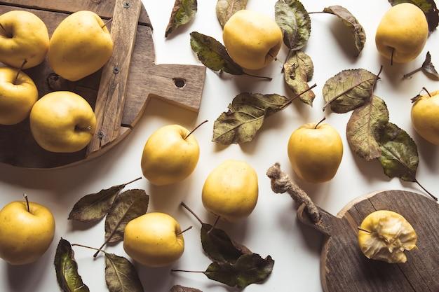 Gelbe äpfel auf einem geschnittenen brett im vintage-stil