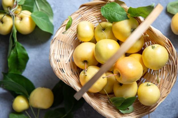 Gelbe äpfel im weidenkorb auf grau