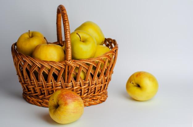 Gelbe äpfel in einem korb auf weiß. gartenarbeit und erntezeit