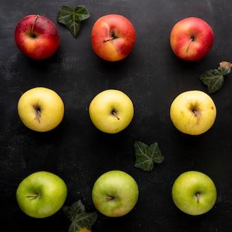 Gelbe äpfel von oben mit grünen und roten äpfeln auf einem schwarzen hintergrund