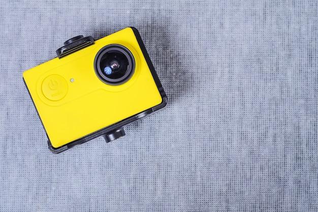 Gelbe aktionskamera auf stoffbeschaffenheitshintergrund.