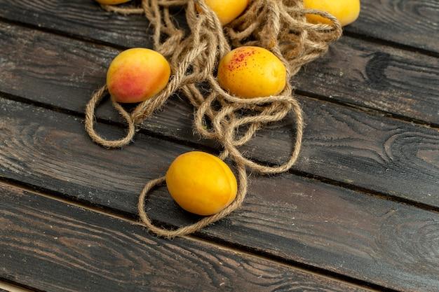 Gelbe aprikosen der draufsicht milde und frische früchte auf dem braunen rustikalen hintergrund