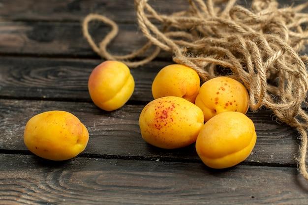 Gelbe aprikosen der vorderansicht milde und frische früchte auf dem braunen rustikalen hintergrundfruchtvitaminsommer