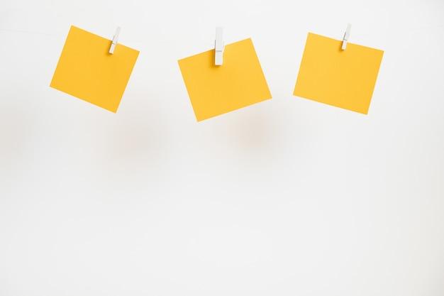 Gelbe aufkleber auf wäscheklammern. exemplar für text.