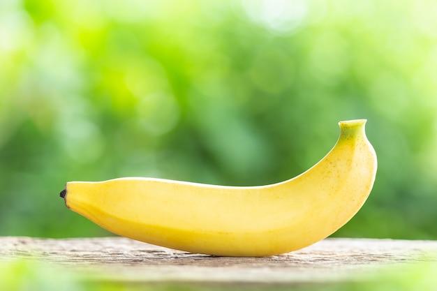Gelbe banane auf holztisch mit grünem unschärfelichthintergrund