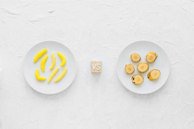 Gelbe banane geformte gummisüßigkeit gegen bananenscheiben auf platte über strukturiertem hintergrund