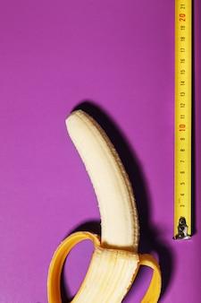 Gelbe banane gemessen durch maßband auf rosa hintergrund