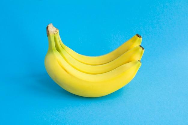 Gelbe bananen auf der blauen oberfläche. nahansicht. fruchtoberfläche.