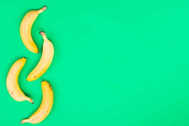 Gelbe bananen auf grünem hintergrund
