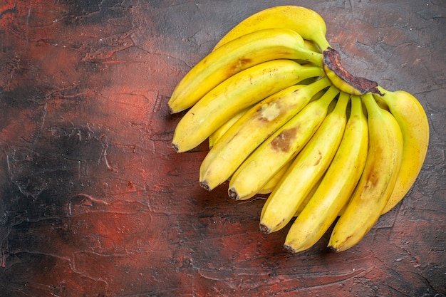 Gelbe bananen der draufsicht auf dunklem hintergrund