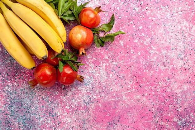 Gelbe bananen der draufsicht mit granatäpfeln auf rosa oberfläche