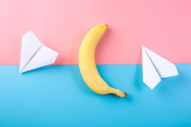 Gelbe bananen- und papierfläche auf pastellhintergrund, draufsicht.