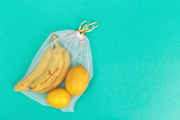 Gelbe bananen und zitrone in wiederverwendbaren öko-beuteln. frisches obst in säcken zur aufbewahrung von lebensmitteln. plastikfreies konzept.