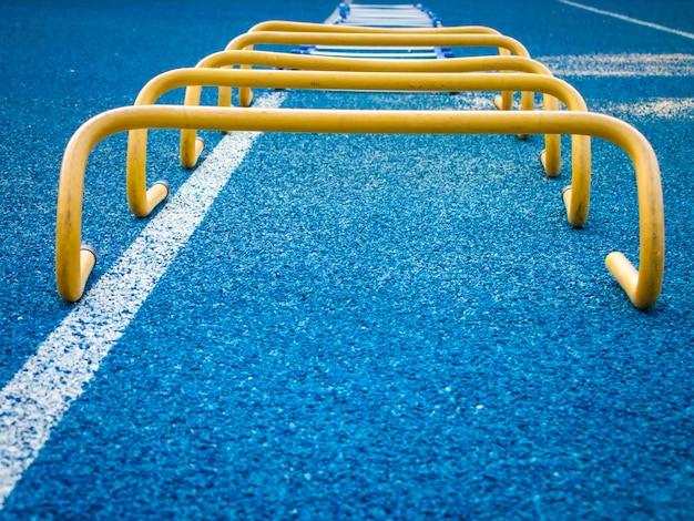 Gelbe bananenhürden richteten sich voreinander auf einem blauen rasenfeld auf