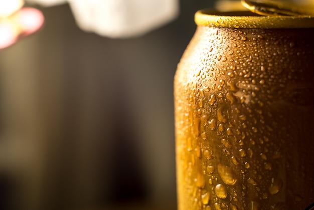 Gelbe bierdosenahaufnahme in den tröpfchen des kalten wassers