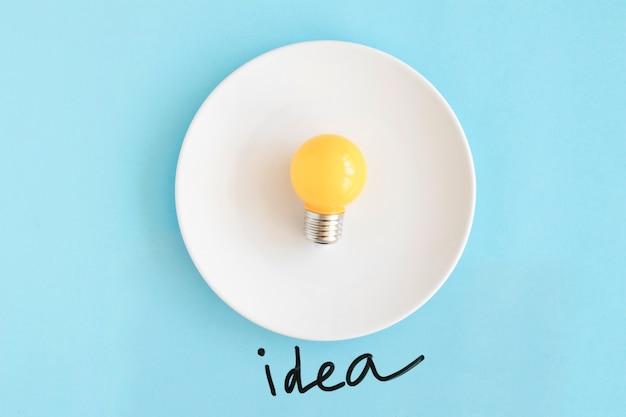 Gelbe birne auf weißer platte mit ideentext auf blauem hintergrund