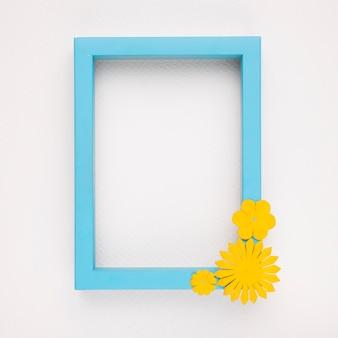 Gelbe blume auf dem hölzernen blauen rahmen gegen weißen hintergrund
