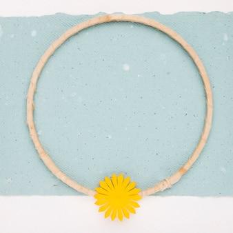 Gelbe blume auf dem leeren kreisholzrahmen über dem papier