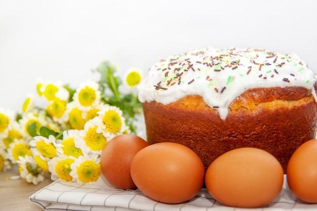 Gelbe blume des osterkuchens und der farbigen eier blüht auf hintergrund