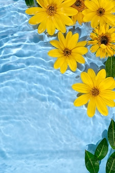 Gelbe blumen auf der wasseroberfläche. schöner wasserwellenhintergrund für die produktpräsentation. platz kopieren