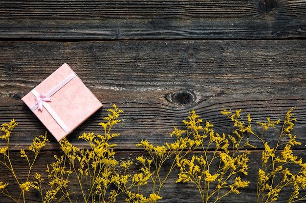 Gelbe blumen auf hölzernem hintergrund