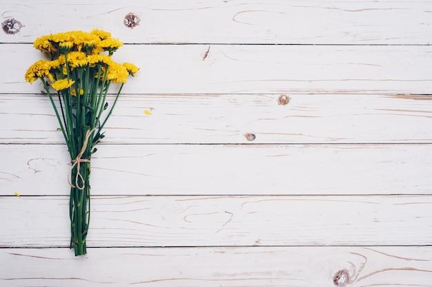 Gelbe blumen des straußes, draufsicht auf weiße hölzerne hintergrundbeschaffenheit mit kopienraum