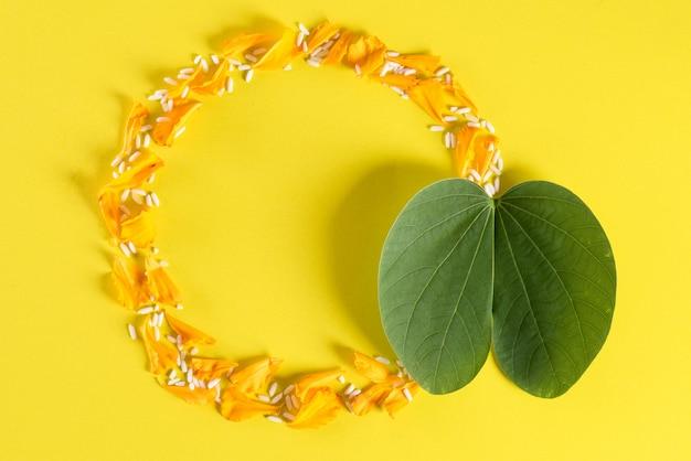 Gelbe blumen, grünes blatt und reis auf gelb