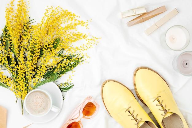 Gelbe blumen, kaffeetasse und stilvolle schuhe mit weiblichen accessoires im bett. flache lage, ansicht von oben