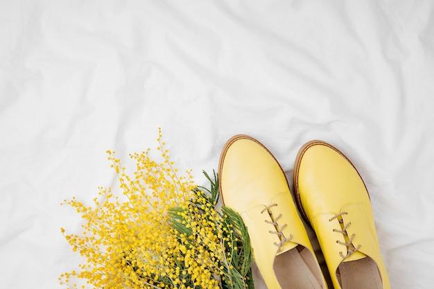 Gelbe blumen und stilvolle schuhe im bett. flache lage, ansicht von oben