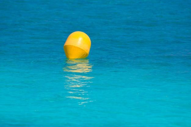 Gelbe boje, die in mittelmeertürkismeer schwimmt