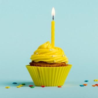 Gelbe brennende kerzen auf dekorativen muffins mit buntem stern besprüht gegen blauen hintergrund
