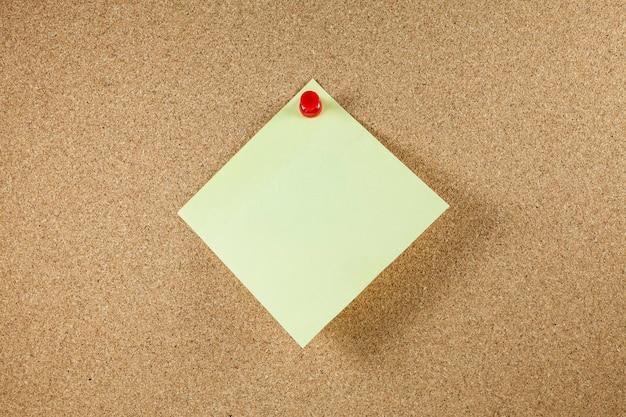Gelbe briefpapiere auf korkbretthintergrund.