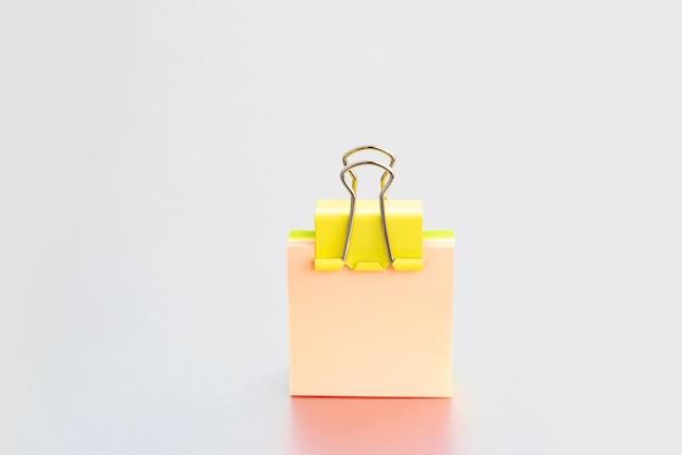 Gelbe büroklammer auf rosa haftnotizen