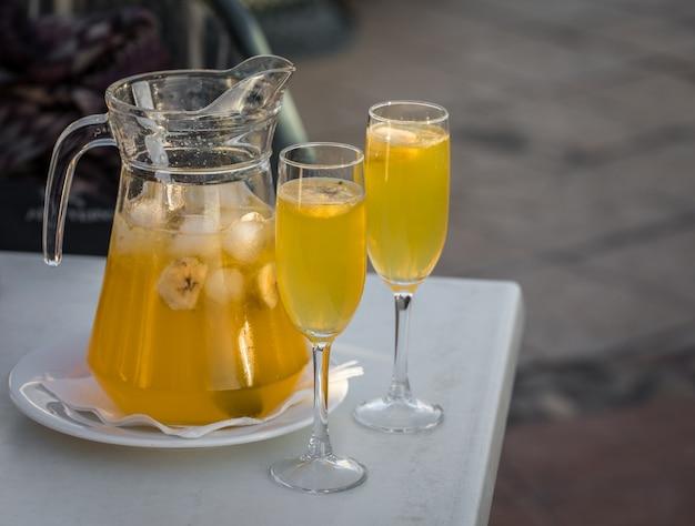 Gelbe champagner-sangria, serviert in einer tasse mit zwei gläsern