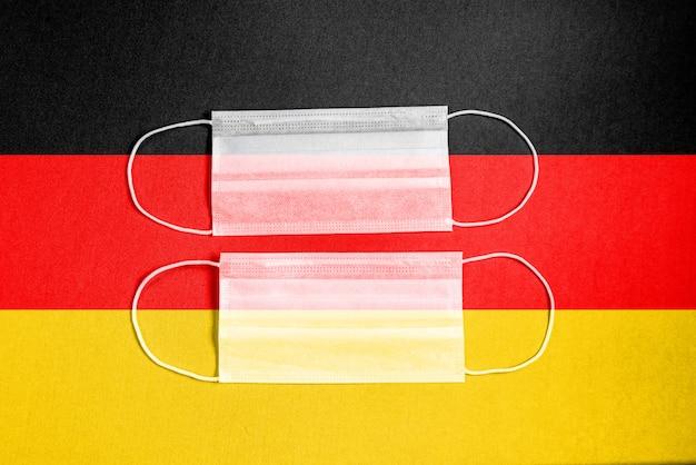 Gelbe chirurgische maske mit deutschlandflagge
