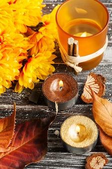 Gelbe chrysantheme, brennende goldene kerzen und blätter