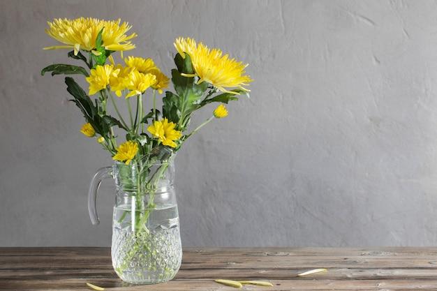 Gelbe chrysantheme im glaskrug auf einem holztisch