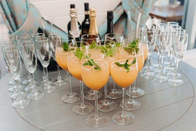 Gelbe cocktails mit minzblättern in gläsern auf dem tisch drinnen