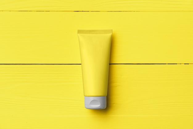Gelbe cremetube auf gelbem hölzernem hintergrund