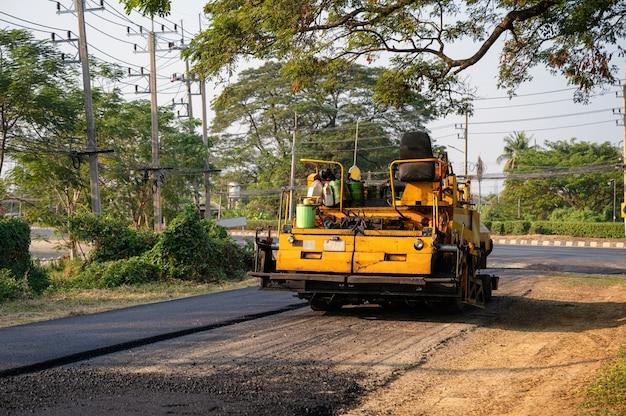 Gelbe dampfwalze oder bodenverdichter, die auf asphaltautobahnstraße auf der baustelle arbeiten