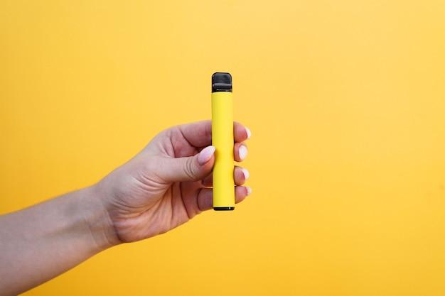 Gelbe elektronische einwegzigarette in einer weiblichen hand. hellgelber hintergrund. vape mit melonen-, ananas- oder zitronengeschmack