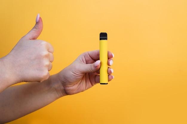 Gelbe elektronische einwegzigarette in weiblicher hand. hand zeigt daumen hoch. alternative zu normalen zigaretten. hellgelber hintergrund. vape mit melonen-, ananas- oder zitronengeschmack
