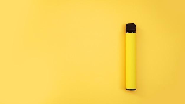 Gelbe elektronische wegwerfzigarette auf hellgelbem hintergrund. vape mit melonen-, ananas- oder zitronengeschmack