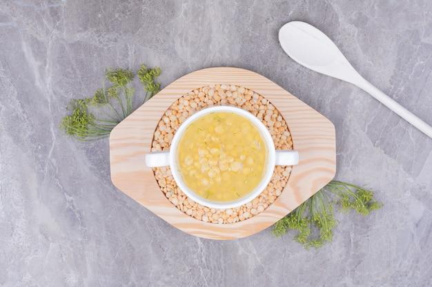 Gelbe erbsenbohnensuppe in einem weißen teller auf dem holzbrett Kostenlose Fotos