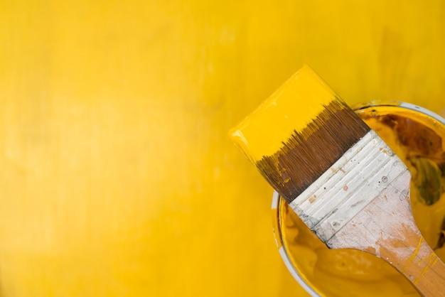 Gelbe farbe, die aus der bürste heraus spritzt.