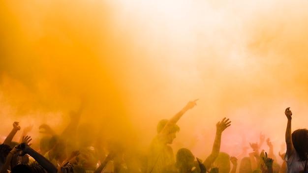 Gelbe farbe explodiert über der menge, die holi festival genießt