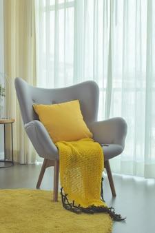 Gelbe fertigkeit und gelbe kisseneinstellung auf grauer farbleichtem lehnsessel im wohnzimmer