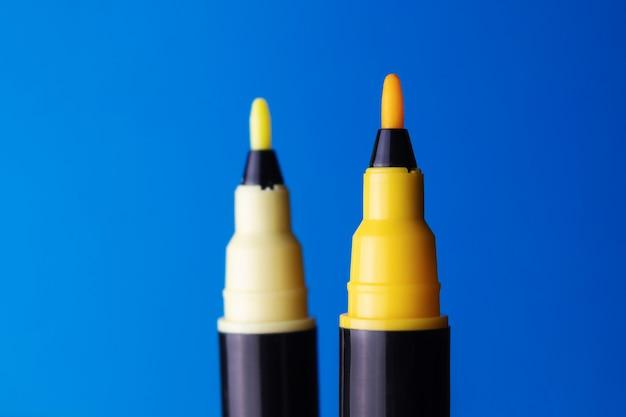 Gelbe filzstiftnahaufnahme auf einem blauen hintergrund.