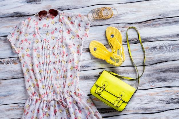 Gelbe flip-flops und bluse. lime geldbörse, bluse und armbänder. trendige kleidung und accessoires für damen. beste preise im modegeschäft.