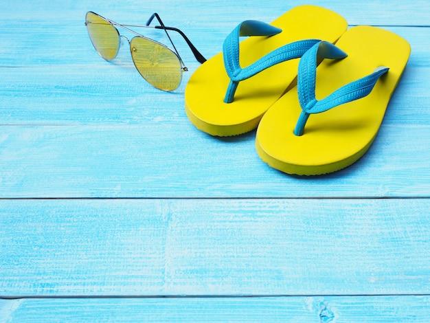 Gelbe flipflopschuhe und -sonnenbrille auf blauem hölzernem hintergrund